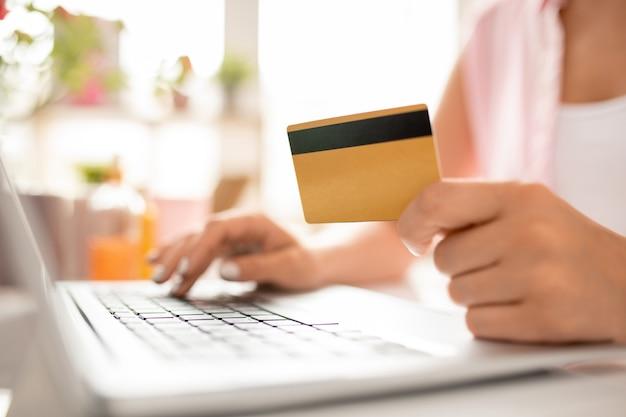 Eigentijdse vrouwelijke shopper met plastic kaart die haar persoonlijke gegevens invoert om online bestelling te betalen