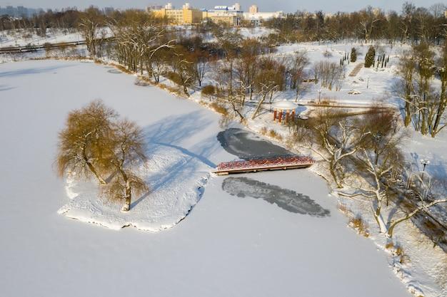 Eiland aan een meer met een brug in het winter loshitsky park minsk, wit-rusland