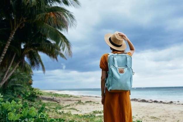 Eiland reizen vrouw rugzak oceaan hoed