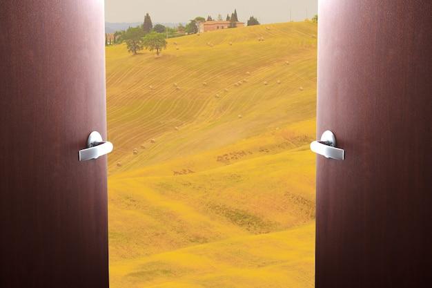 Einde quarantaine covid-19. het begin van reizen, het openen van grenzen. deuren zwaaien open met uitzicht op de velden en wijngaarden van het zonnige toscane, italië