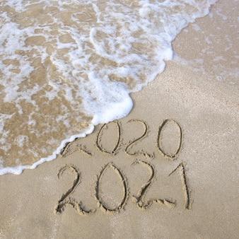 Einde van het jaar 2020-concept. nieuwjaar 2021. inschrijving in het zand op het strand