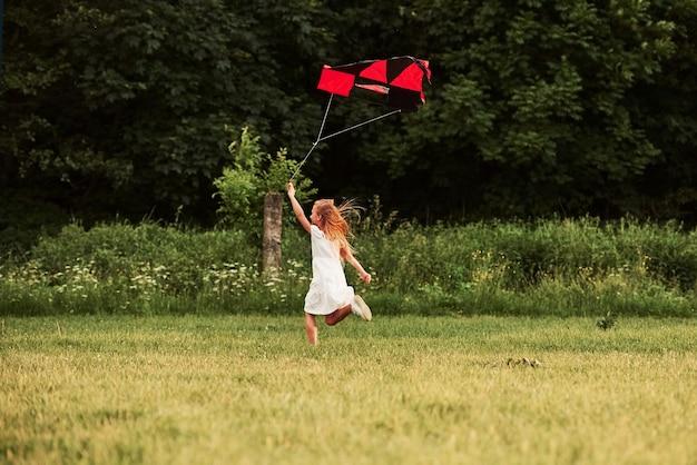 Eindelijk is het zomer. gelukkig meisje in witte kleren veel plezier met vlieger in het veld. prachtige natuur.