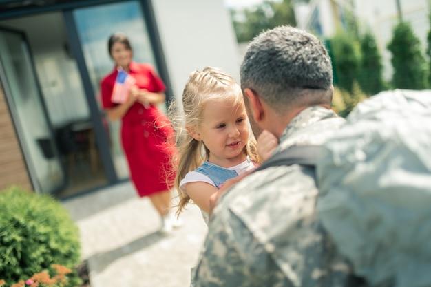 Eindelijk thuis. militaire man komt terug naar huis en ziet zijn vrouw en dochter in de buurt van het huis