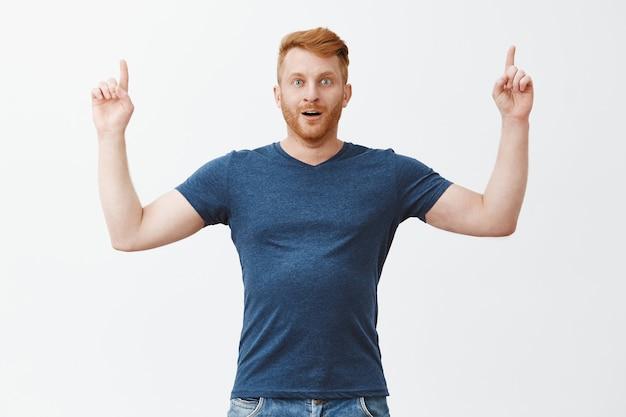 Eindelijk top van succes bereiken, kan niet geloven. portret van onder de indruk opgewonden en verbaasde knappe volwassen roodharige met borstelharen in blauw t-shirt, omhoog wijzend met opgeheven handen, gecharmeerd en verbaasd