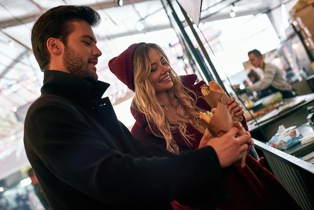 Eindelijk warme broodjes. jong stel koopt sandwiches bij broodjesbar op de straatvoedselmarkt. koud seizoen. jonge blonde vrouw lacht