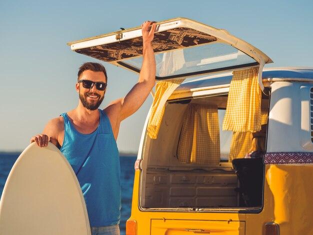 Eindelijk zomer! glimlachende jonge man leunend op het skimboard en hand op de deur van de kofferbak terwijl hij op het strand staat