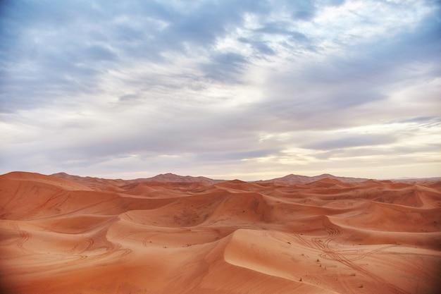 Eindeloos zand van de sahara-woestijn, de hete, brandende zon schijnt op de zandduinen. marokko merzouga