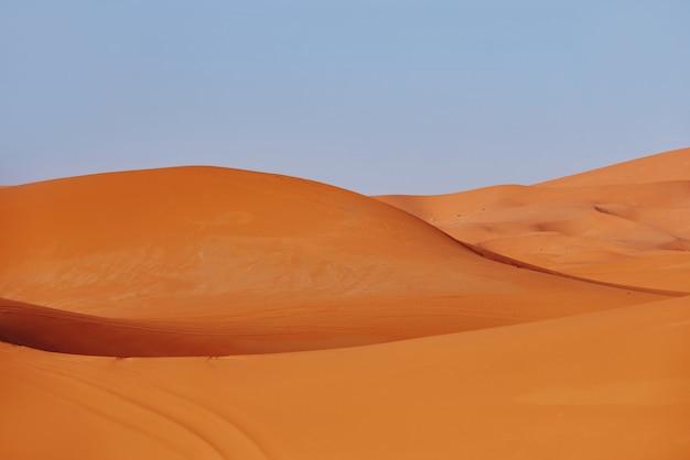 Eindeloos zand van de saharawoestijn, de hete brandende zon schijnt op de zandduinen. marokko merzouga