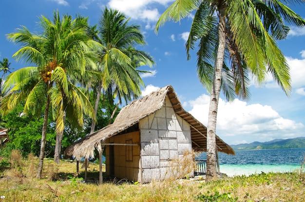 El nido eilandhoppen. oude bamboehut op het strand. palawan, filippijnen