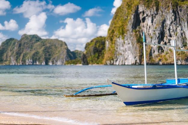 El nido. sluit omhoog van traditionele filippijnse boot op kust met pinagbuyutan-eiland op achtergrond