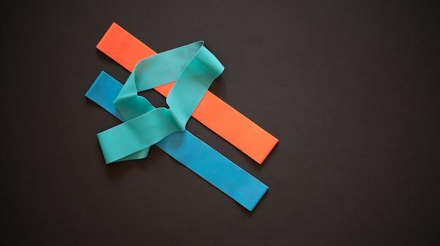 Elastische banden voor fitness van een andere kleur op een donkere achtergrond bovenaanzicht