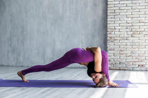 Elastische vrouw die zich uitstrekt op een tapijt