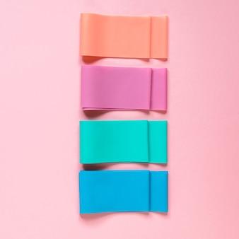 Elastische weerstandsbanden op de roze achtergrondaccessoires voor fitnessapparatuur