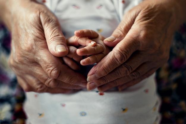Eldery-handen die pasgeboren jonge handen houden; grootvader