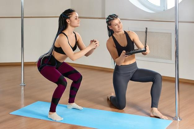 Elearning oefeningen voor kracht en flexibiliteit in een paalacrobatiekstudio vrouw turnster kijkt lessen op laptopscherm