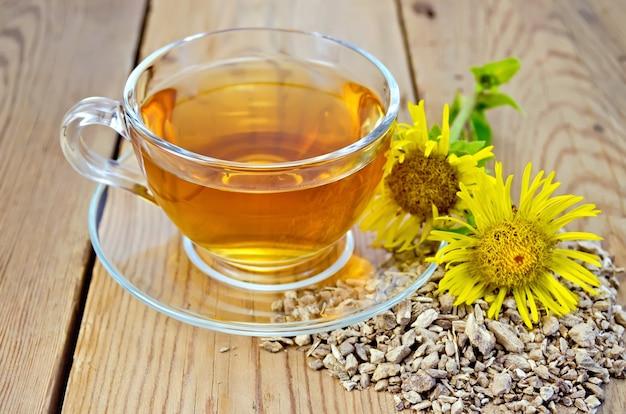 Elecampane wortel, verse gele bloem elecampane thee in een glazen beker op een houten bord