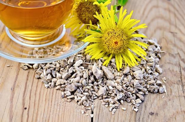 Elecampane wortel, verse gele bloem elecampane, thee in een glazen beker op houten planken