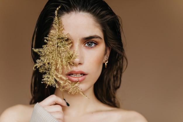Elegant bleek meisje met gouden oorringen die verbazing uitdrukken. close-up shot van sensuele brunette dame met plant.