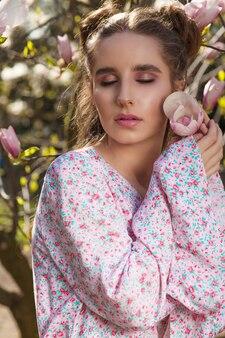 Elegant brunette meisje met mooie make-up poseren in de buurt van de bloeiende magnoliaboom