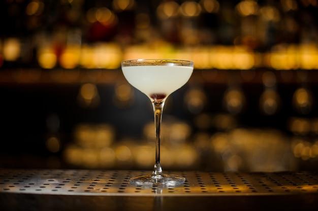 Elegant cocktailglas verse zoetzure cocktail op de achtergrond van gouden licht in staaf
