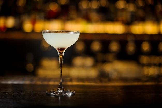 Elegant cocktailglas verse zoetzure cocktail op de onscherpe achtergrond van gouden licht in staaf