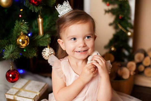 Elegant europees meisje in een lichte jurk bij de kerstboom houdt haar handen voor haar gezicht