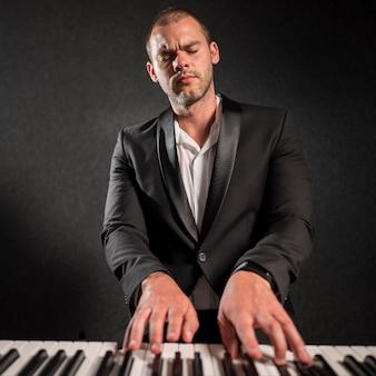 Elegant geklede artiest die keyboards speelt