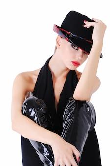 Elegant glamourmeisje in zwarte kleding met modieuze manierhoed