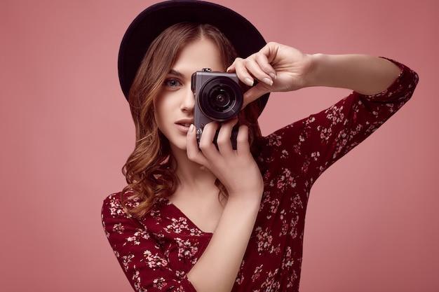 Elegant hipstermeisje in rode kleding, zwarte hoed en glazen met camera