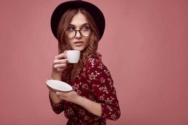 Elegant hipstermeisje in rode kleding, zwarte hoed en glazen met kop van espresso