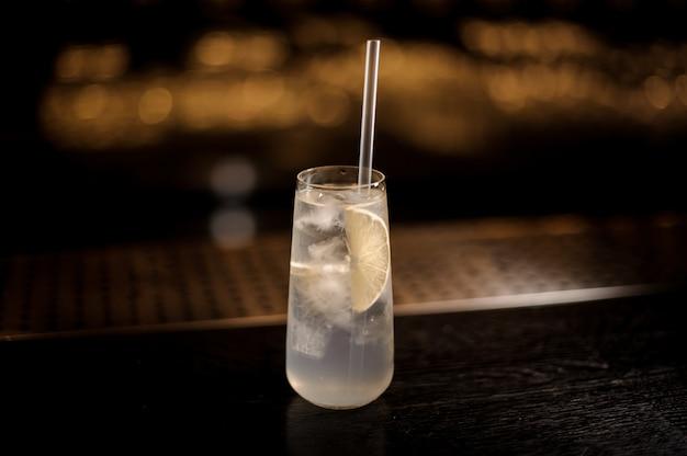 Elegant longdrinkglas gevuld met tom collins cocktail aan de bar