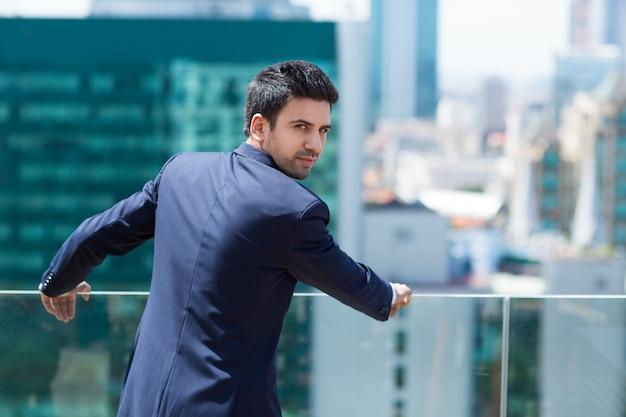Elegant man leunend op een balustrade terug te kijken