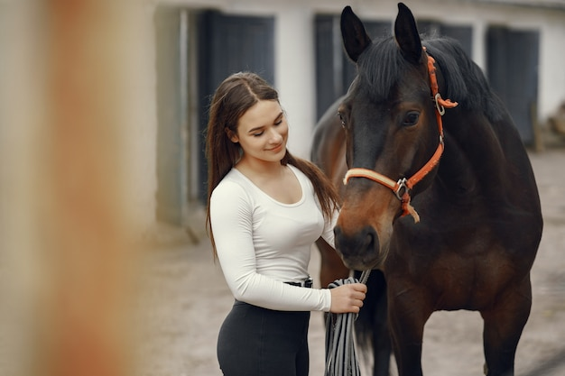 Elegant meisje in een boerderij met een paard