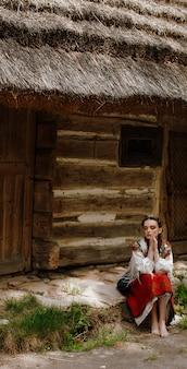 Elegant meisje in een traditionele jurk zit naast het huis