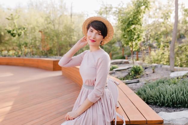 Elegant meisje in lange lichte jurk rusten buiten, zittend op een bankje in prachtig groen park in de ochtend