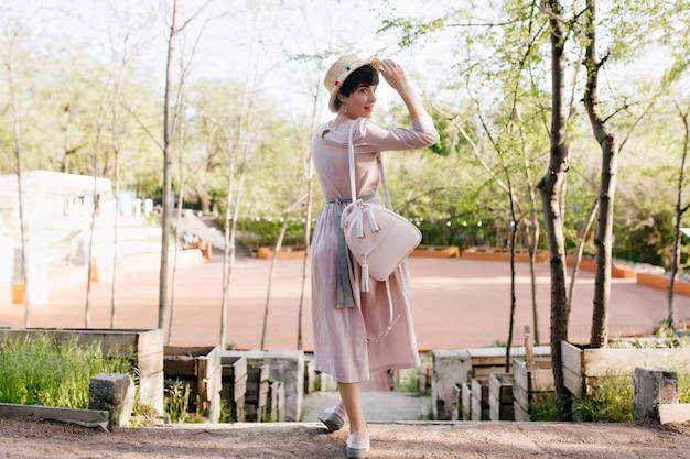 Elegant meisje in ouderwetse kledij die over haar schouder kijkt en strohoed met leuke glimlach houdt