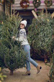 Elegant meisje koopt een kerstboom.
