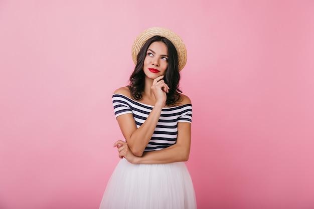 Elegant meisje met een gebruinde huid poseren met peinzende gezichtsuitdrukking