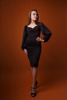 Elegant model in zwarte jurk met diepe halslijn poserend op oranje achtergrond