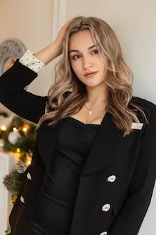 Elegant mooi jong vrouwenmodel in een modieus zwart pak met een luxe blazer staat binnenshuis bij de witte muur