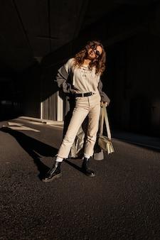 Elegant mooi meisje met krullend haar en zonnebril in modieuze kleding look: lange jas, trui, broek, schoenen en een handtas staat in de stad in het zonlicht en de schaduw. stedelijke vrouwelijke stijl