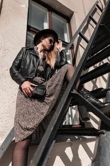 Elegant mooi model meisje in een hoed met zonnebril in een modieuze jurk met een leren jas en een zwarte handtas staat op een metalen trap in de stad