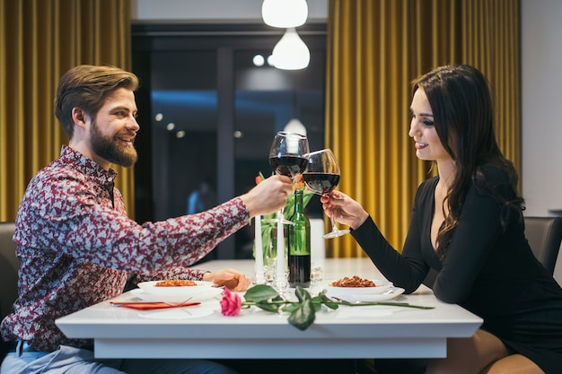 Elegant paar dat met glazen rammelt die diner hebben