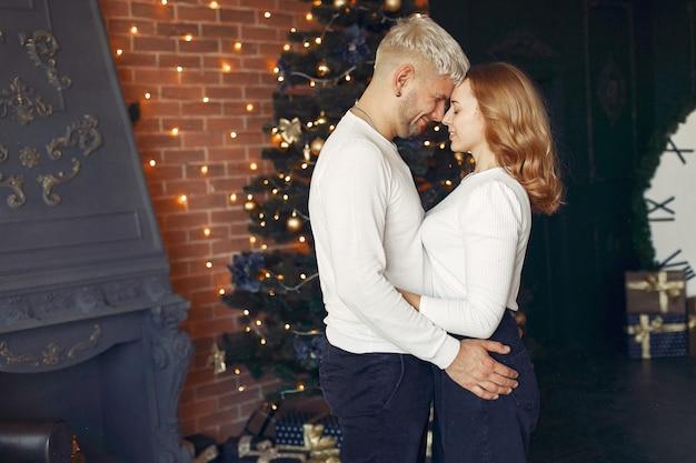 Elegant paar dat zich thuis dichtbij kerstboom bevindt