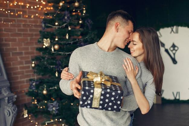 Elegant paar thuis dichtbij kerstboom