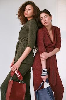 Elegant paar zwarte en aziatische vrouwen in modieuze groene en rode pakken