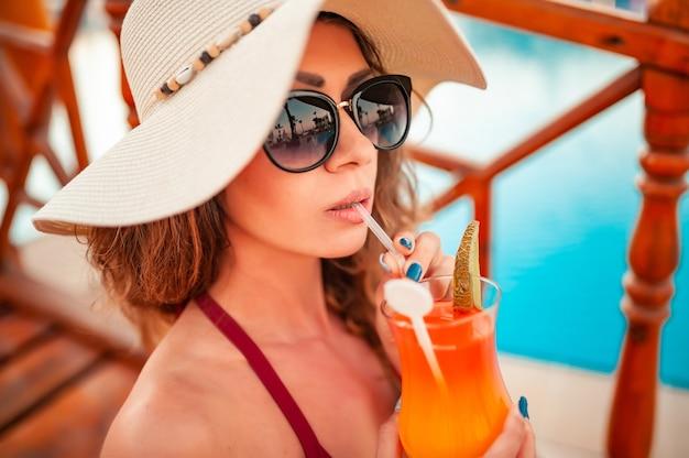 Elegant portret van jong vrij sexy meisje dat een kleurrijke cocktail drinkt bij het zwembad