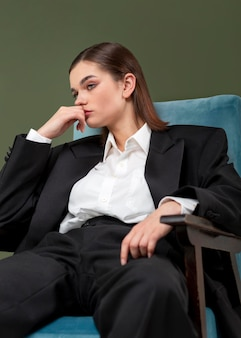 Elegant vrouwelijk model zittend in een fauteuil in een jasje. nieuw vrouwelijkheidsconcept