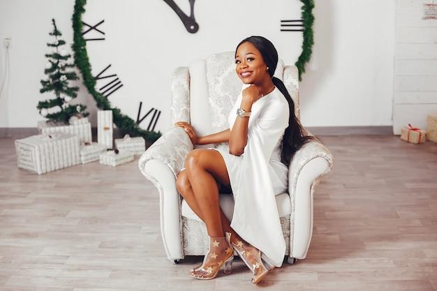 Elegant zwart meisje in een kamer met kerstmis