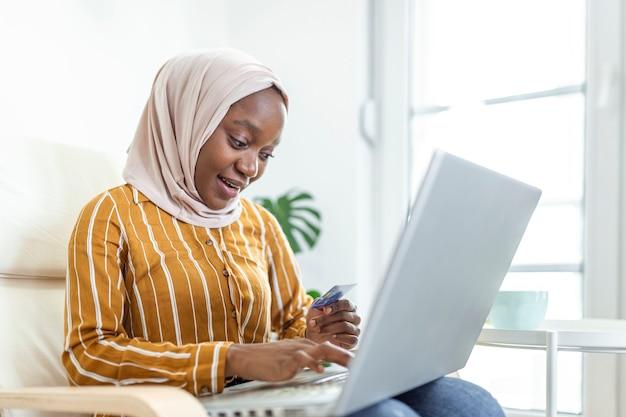 Elegante aantrekkelijke moslimvrouw die mobiele laptop gebruikt die online winkelinformatie zoekt in de woonkamer thuis. portret van een gelukkige vrouw die een product koopt via online winkelen. betalen met creditcard